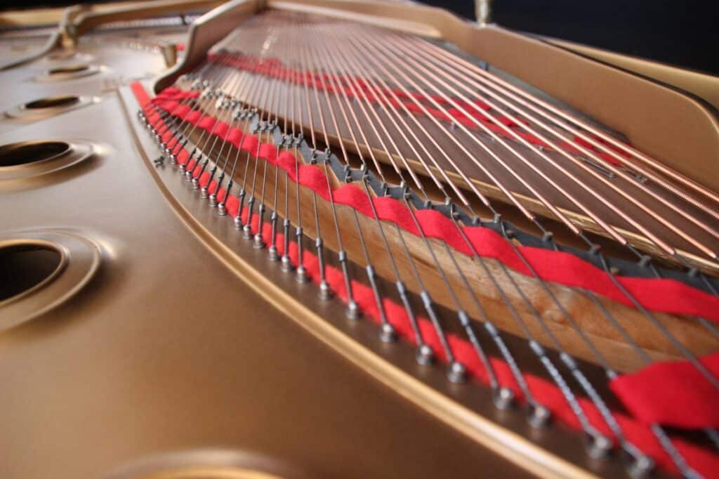Close up photo of the strings inside a grand piano